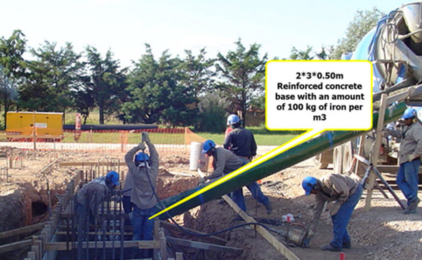 The image shows workers constructing the concrete base.
